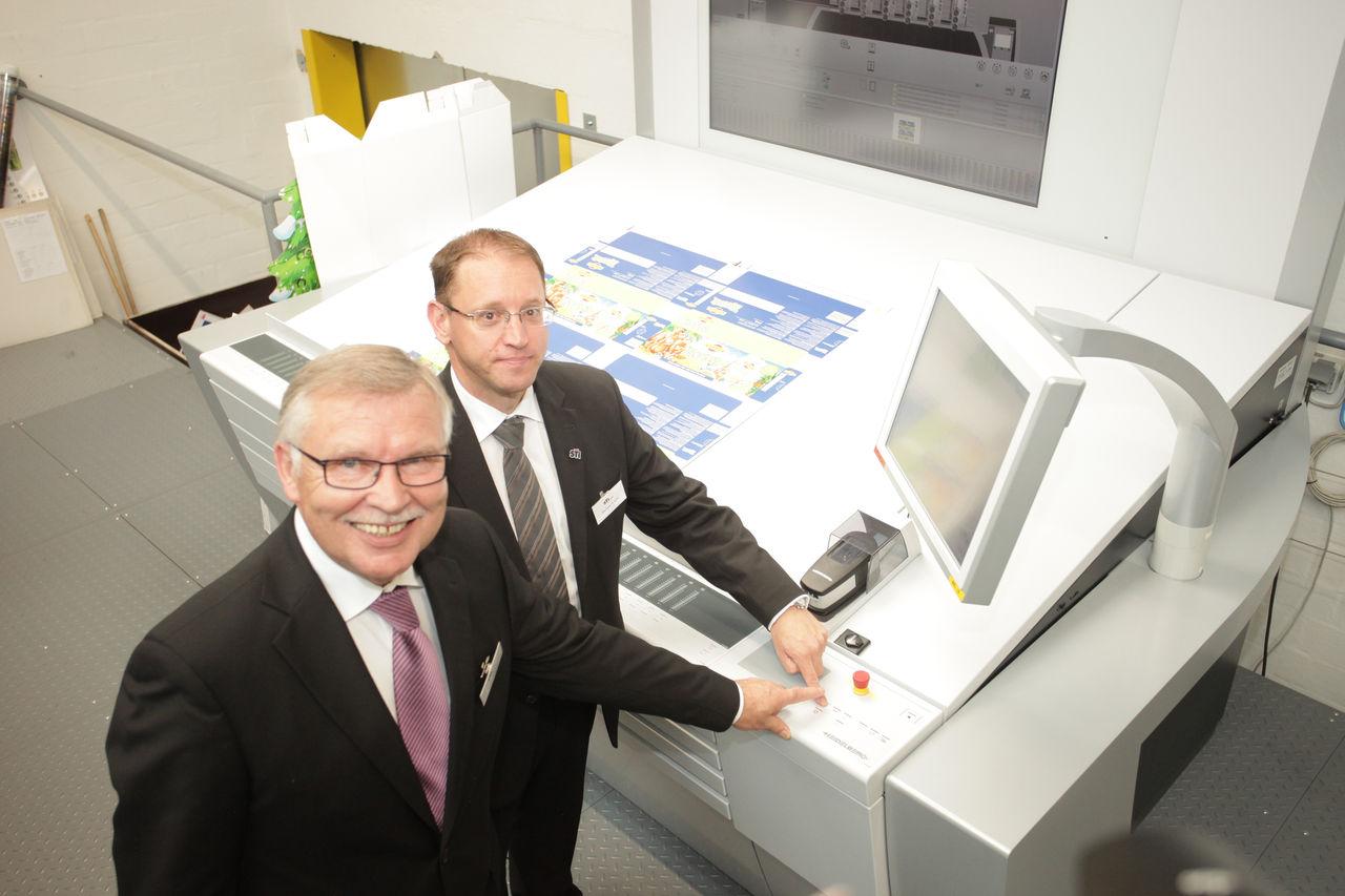 """Auf los geht`s los –Norbert Dietz, Leiter technische Projekte und Werkleiter Michael Busold starten symbolisch die neue Hochleistungs-Druckmaschine """"Heidelberger Speedmaster XL""""."""