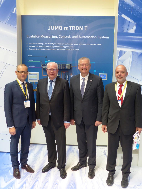 Landrat Bernd Woide (zweiter von rechts), Bürgermeister Dag Wehner (links) und Regionalmanager Christoph Burkard (rechts) haben sich von Bernhard Juchheim (zweiter von links) den JUMO-Stand auf der Hannover Messe präsentieren lassen.
