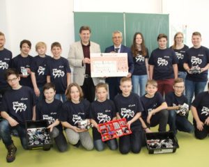 L.A.N. Geschäftsführer Esmail Akbari überreicht den Scheck an Schulleiter Marco Schumacher. Auf dem Bild sind auch die Schüler der Roboter AG und die betreuenden Lehrer zu sehen.