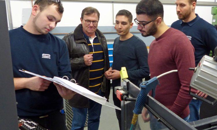 Ein JUMO-Auszubildender zeigt interessierten Jugendlichen die Arbeit im hauseigenen Ausbildungszentrum.