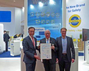 Dr. Jochen Köckler (links), Vorstandsvorsitzender der Deutschen Messe AG, überreicht die Urkunde für die 70. Messeteilnahme an Bernhard (Mitte) und Michael (rechts) Juchheim.