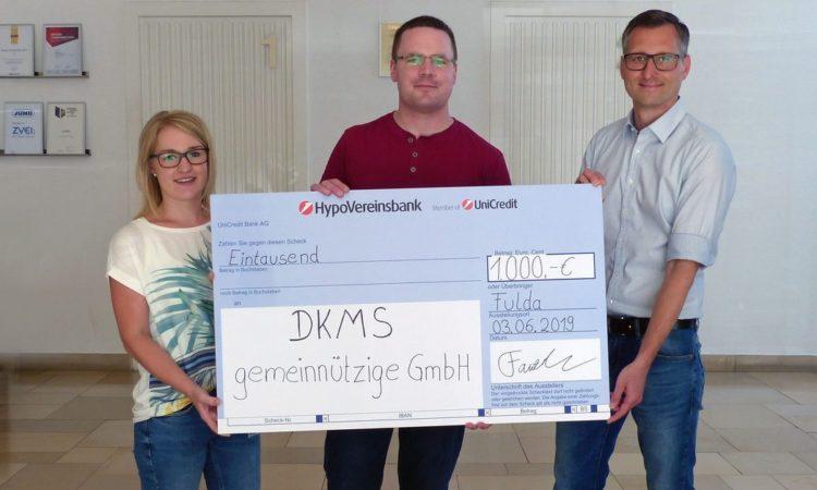 Theresa Kümmel, Mitarbeiterin der JUMO-Marketingabteilung (links) und Marketingleiter Michael Diegelmann (rechts) übergeben den symbolischen Scheck in den Räumen der JUMO GmbH & Co. KG an den DKMS-Vertreter Michael Möller.
